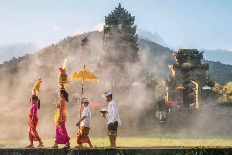 Ubud, Bali - 30 de julho de 2016 Mostrando o homem tradicional do Balinese e ofertas cerimoniais fêmeas do roupa e as religiosas imagens de stock royalty free