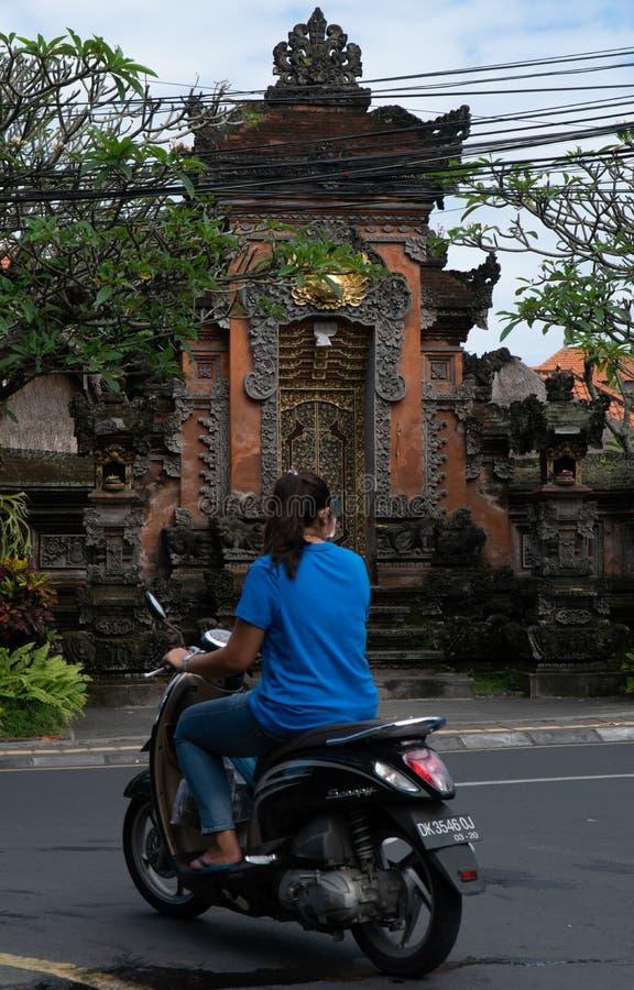 Ubud, Bali, Indonésia 3 de maio de 2019: A mulher não identificada monta o 'trotinette' de motor em Ubud, Bali, Indonésia imagens de stock royalty free