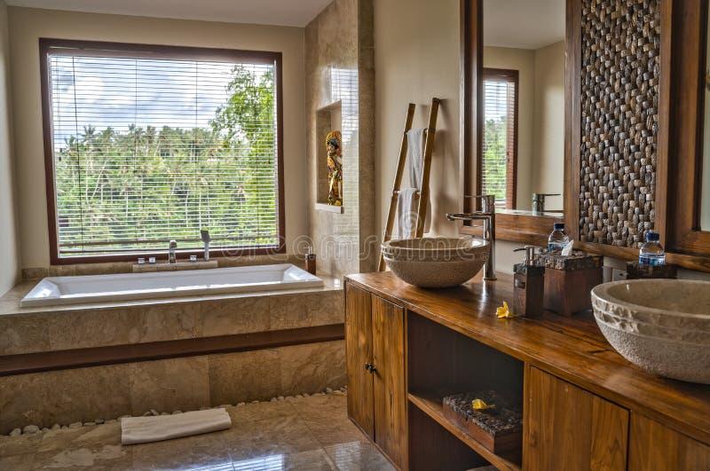 Ubud, Bali, Indonésia - em janeiro de 2019: Interior do banheiro do hotel de luxo com elementos do projeto tradicional do Balines foto de stock royalty free