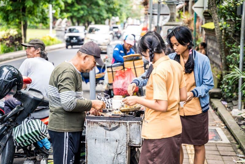 Ubud, Bali, Indonésia - em janeiro de 2019: Meninas no alimento de compra da farda da escola de um vendedor ambulante durante a p foto de stock royalty free