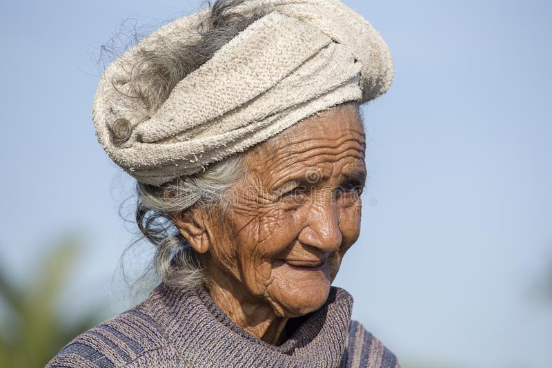 Portrait old poor woman to Bali island. Inhabitants of Bali are kind and friendly even in old age royalty free stock images