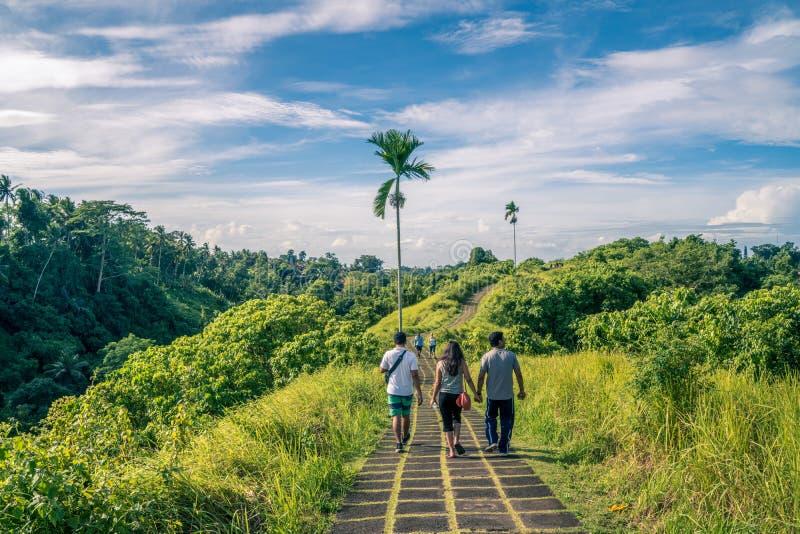 Ubud Bali, Indonesien - Januari 2019: turist- vägledd tagande turnerar av kanten går i Ubud arkivfoto