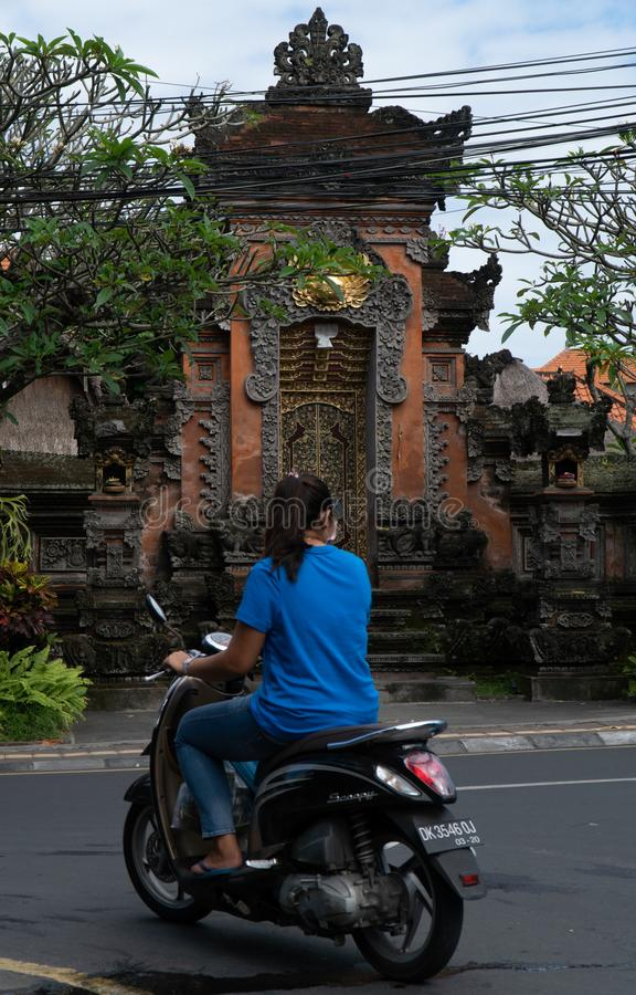 Ubud Bali, Indonesien Maj 3, 2019: Den oidentifierade kvinnan rider motorsparkcykeln i Ubud, Bali, Indonesien royaltyfria bilder