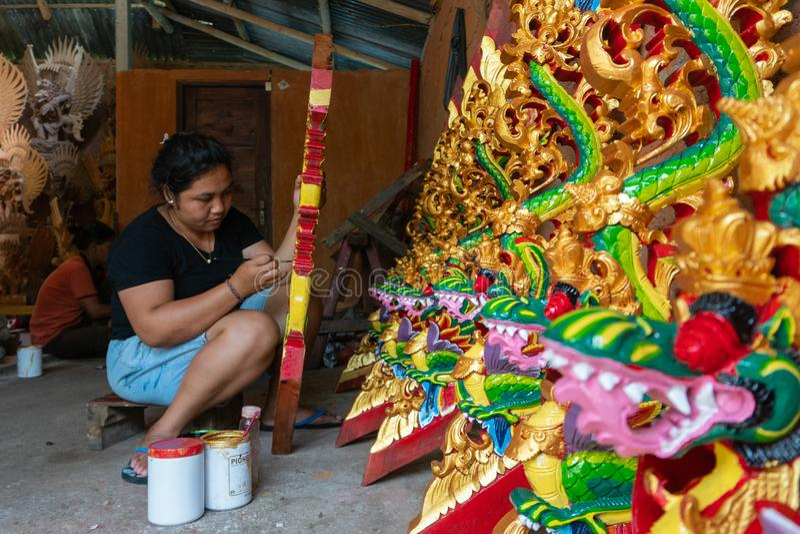 UBUD/INDONESIA-APRIL 27 2019: En kvinnlig hantverkare fr?n Ubud g?r draken som snider och f?rgar den att anv?nda som ?r ljust och arkivfoton