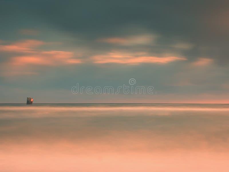 Uccelli di mare sul masso che attacca fuori dal mare ondulato liscio Anche oceano ondulato Orizzonte scuro con gli ultimi raggi d immagine stock
