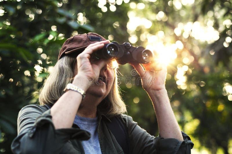 Uccelli di sorveglianza della donna anziana con il binocolo immagini stock libere da diritti