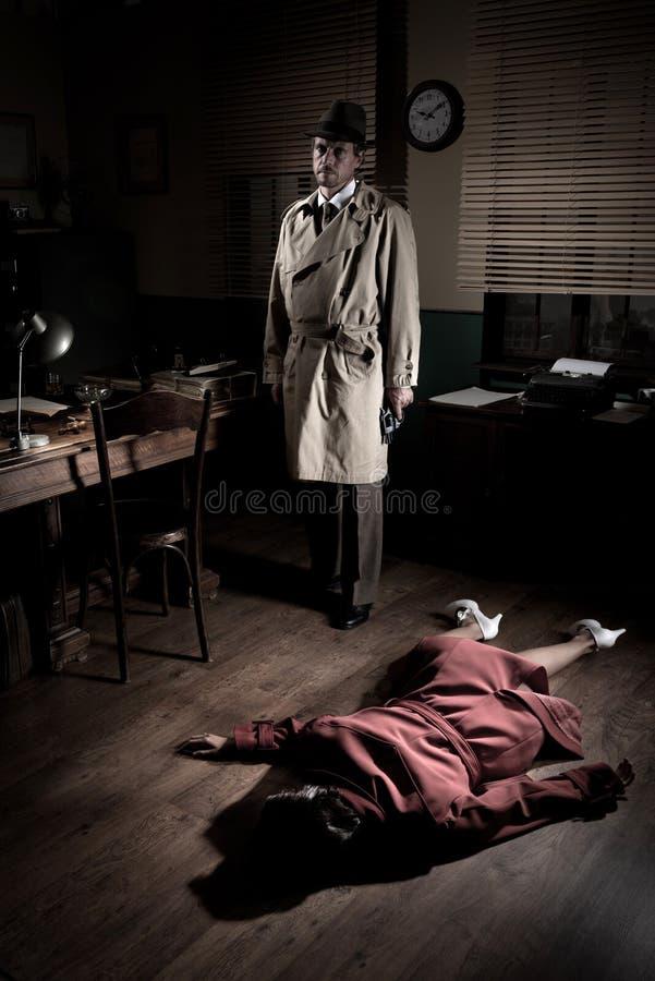 Uccisore con la donna morta che si trova sul pavimento fotografia stock