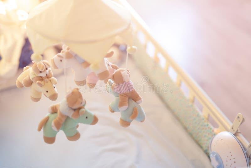 Ucha do bebê do close-up com o móbil animal musical na sala do berçário Brinquedo tornando-se Hanged com os animais macios do lux foto de stock