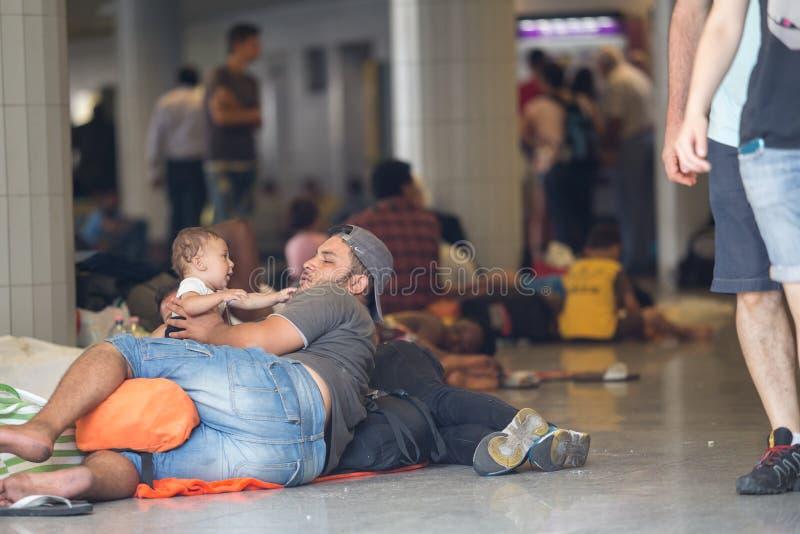 Uchodźca bawić się z jego dzieckiem przy Keleti dworcem w Budapest obraz stock