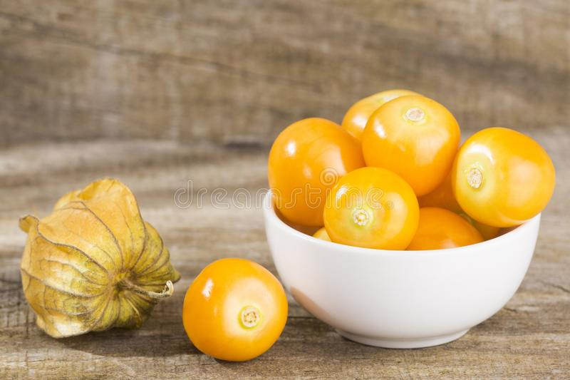 Uchuva delicious tropical fruit - Physalis peruviana. Physalis physalis, golden, gooseberry isolated on wooden background - Physalis peruviana stock images