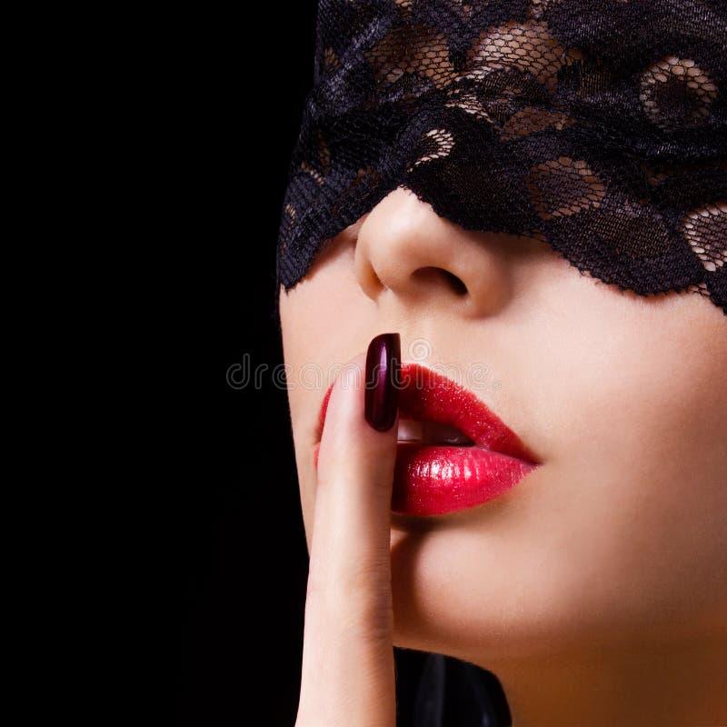 Ucichnięcie. Seksowna kobieta z palcem na jej czerwony warg pokazywać shush. Erotyczna dziewczyna z koronki maską nad czernią obrazy stock