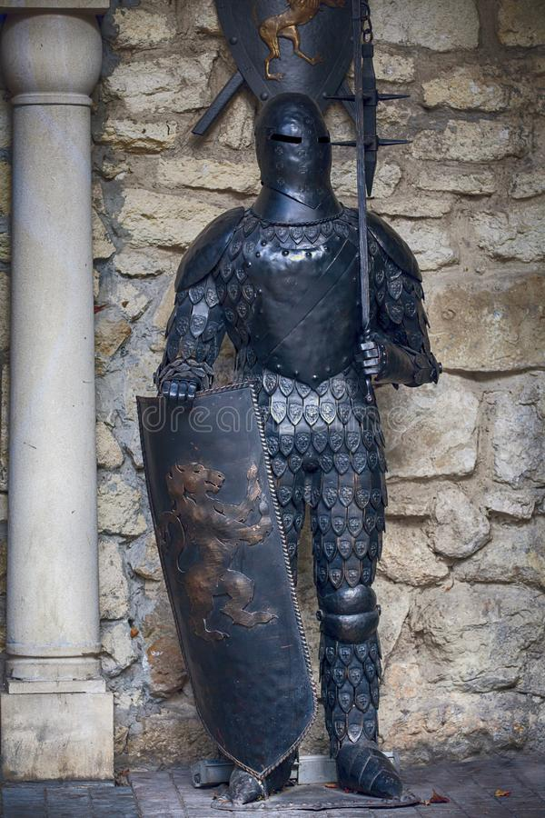 Ucrânia, Lviv - 4 de outubro de 2018 Knight na armadura completa com uma espada na perspectiva das paredes antigas imagens de stock