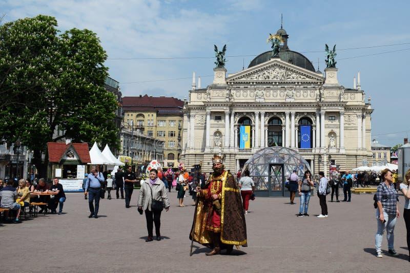 Ucr?nia, Lviv - em maio de 2019: um homem no traje do carnaval do rei Danylo Galitsky na perspectiva do teatro de Opera dentro fotografia de stock