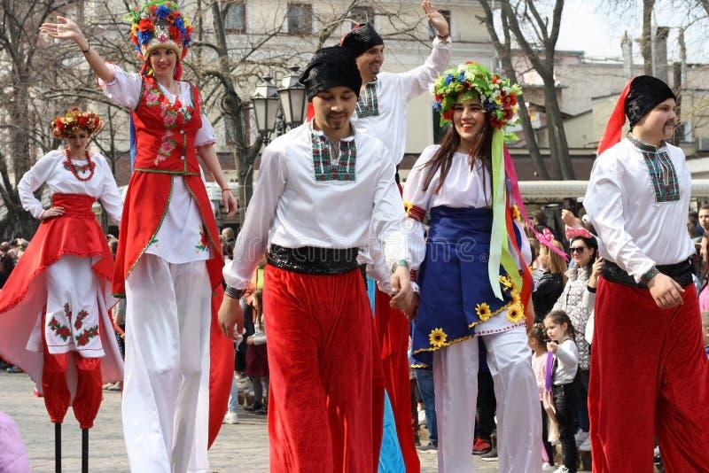 Ucrânia, Odessa - 1º de abril de 2019: Um grupo colorido de dançarinos da rua em pernas de pau em trajes ucranianos Parada do ris imagem de stock royalty free