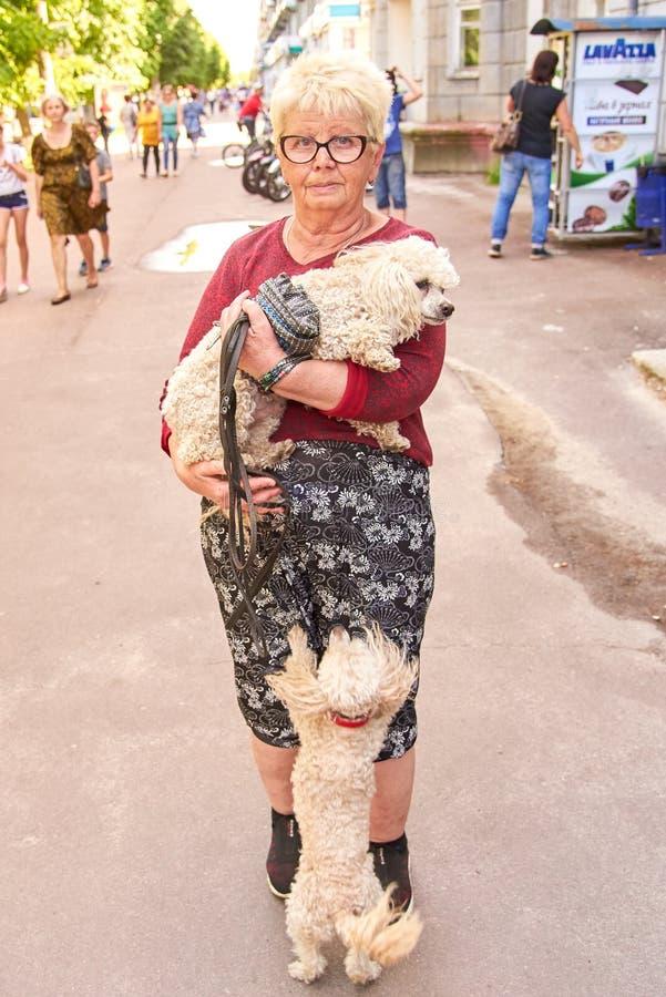 Ucrânia, Shostka - 1º de junho de 2019: Mulher idosa que guarda uma caniche em seus braços em uma rua da cidade fotos de stock