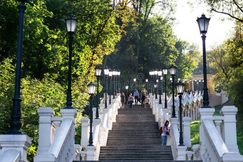 UCRÂNIA, KIEV-SEPTEMBER 24,2017: Povos que andam abaixo da escadaria com as luzes que conduzem ao parque na rua de Naberezhnaya fotografia de stock royalty free