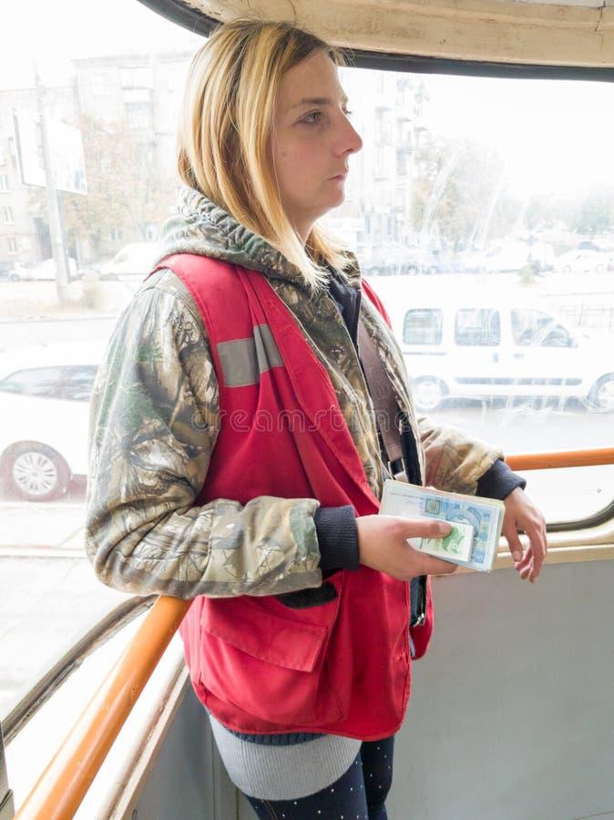 Ucrania, Kiev - 12 de setiembre de 2019: una joven inspector de uniforme rojo y amarillo de trabajo está de pie con dinero y entr fotos de archivo libres de regalías
