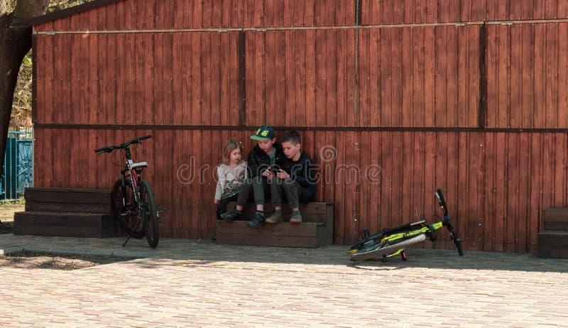 Ucrania, Kremenchug - abril de 2019: Los niños son el usar los smartphones en vez de las bicicletas que montan foto de archivo libre de regalías