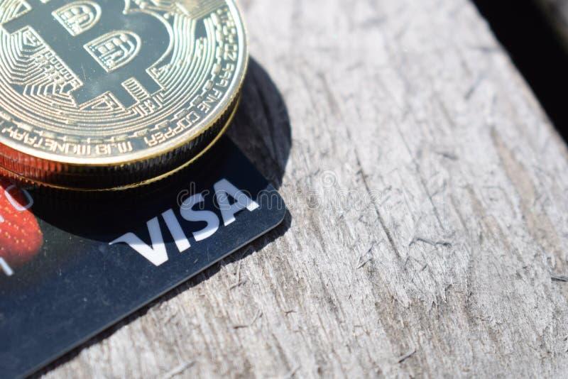 Ucrania, Kremenchug - marzo de 2019: Bitcoin en tarjeta Visa foto de archivo