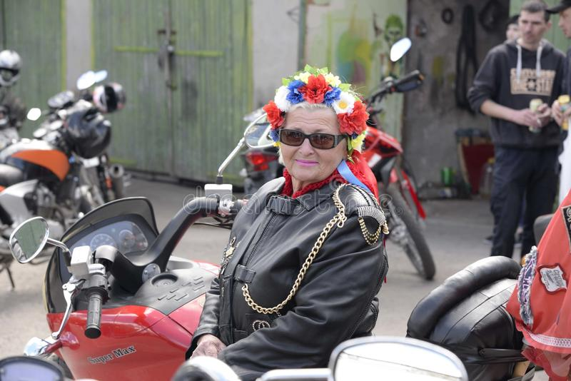 UCRANIA, SHOSTKA - ABRIL 28,2018: La mujer mayor, motorista se sienta en su motocicleta en el parque de la ciudad de Shostka imagen de archivo