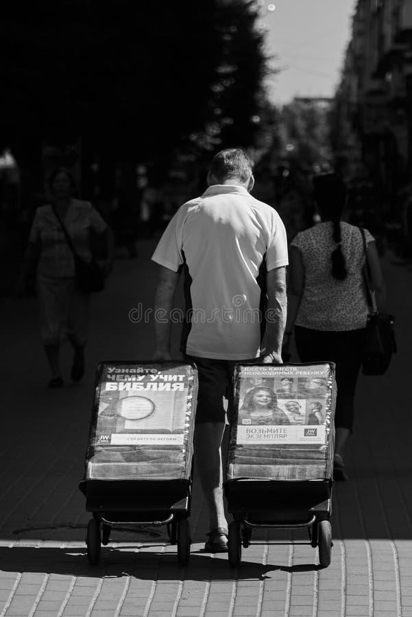 Ucrania, Shostka-24 de agosto de 2019: Un hombre rota carretas. En uno está escrito: Descubre lo que la Biblia enseña imagen de archivo