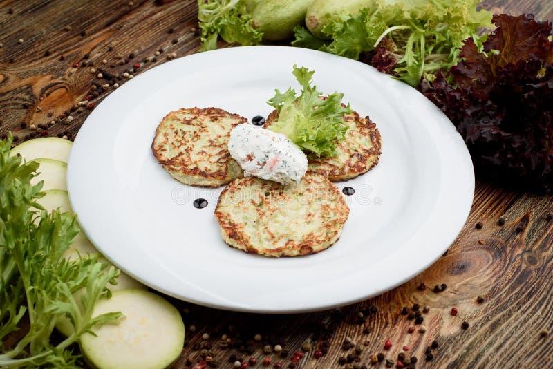 Ucraniano tradicional, prato do russo - Draniki Panquecas de batata na placa branca com creme de leite no fundo de madeira imagem de stock