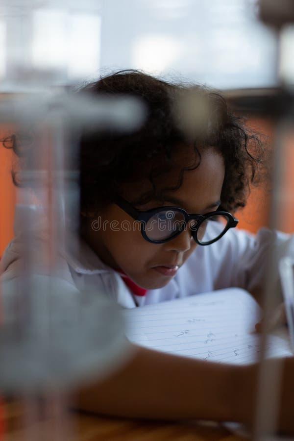Uczeń pisze na papierze w laboratorium zdjęcia royalty free