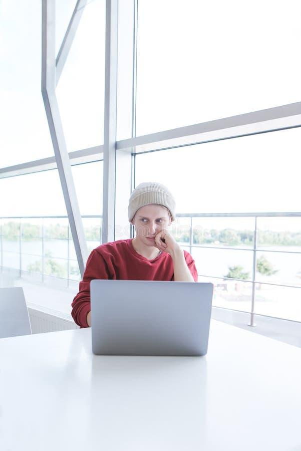 Uczeń używa laptop w lekkiej kawiarni z nowożytnym wnętrzem Portret młody biznesmen obraz stock