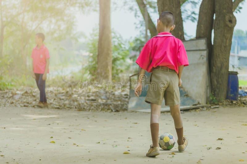 Uczeń cieszy się bawić się starego futbol z jego przyjaciółmi na ziemi zdjęcia stock