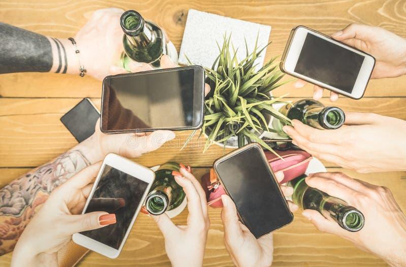 Uczeń grupa uzależnia się zabawę wpólnie używa smartphones - zdjęcie stock