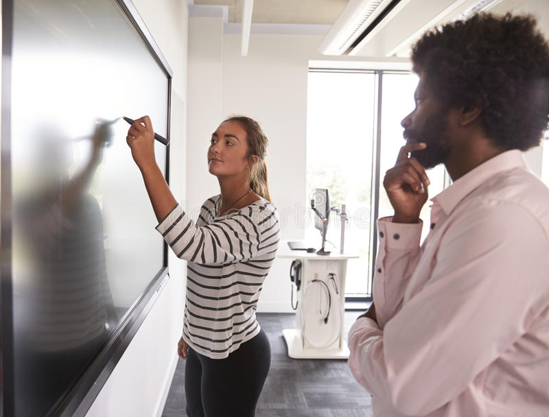 Uczeń I adiunkt Dyskutujemy projekt Na Interaktywnym Whiteboard zdjęcia royalty free