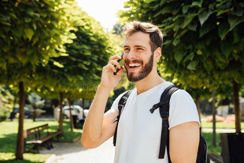 Uczeń opowiada przy telefonem komórkowym z plecakiem zdjęcia royalty free