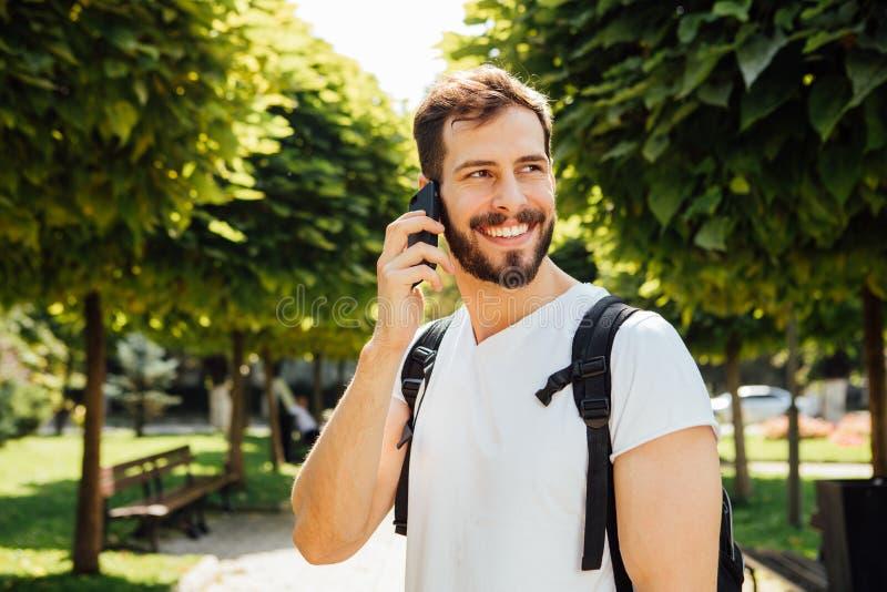 Uczeń opowiada przy telefonem komórkowym z plecakiem obrazy royalty free