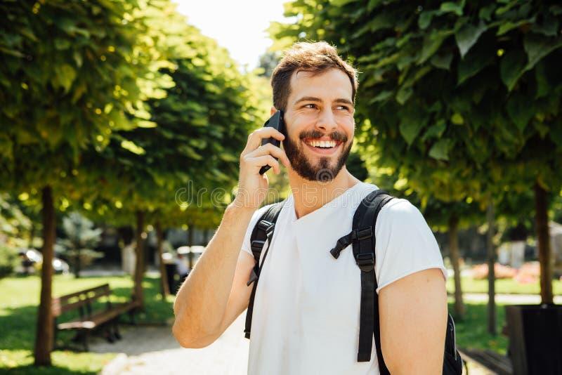 Uczeń opowiada przy telefonem komórkowym z plecakiem obrazy stock