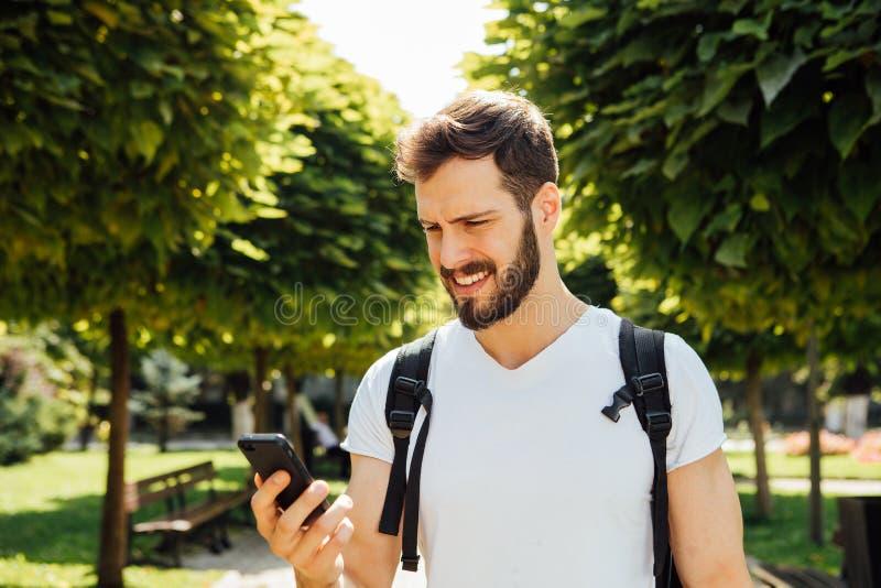 Uczeń opowiada przy telefonem komórkowym z plecakiem fotografia stock