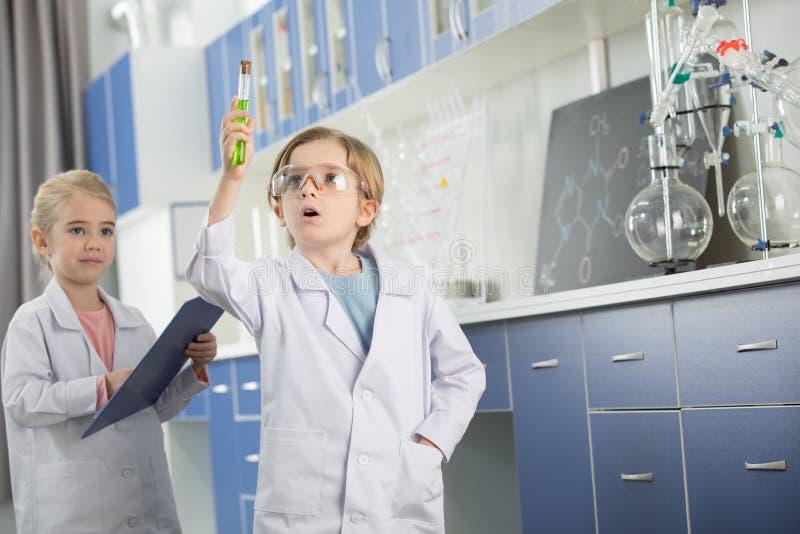 Uczeń patrzeje próbkę w próbnej tubce w lab żakiecie obrazy stock