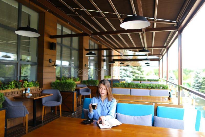 Uczeń pije coffe i obsiadanie z przy kawiarnią smartphone i notatnikiem zdjęcie royalty free