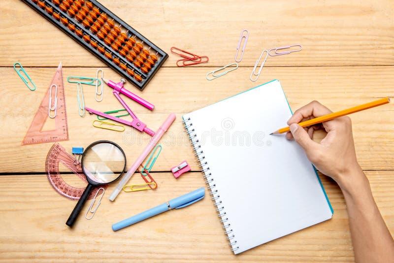 Uczeń pisze w notatniku z szkolnymi dostawami i materiały na drewnianym stole zdjęcia royalty free