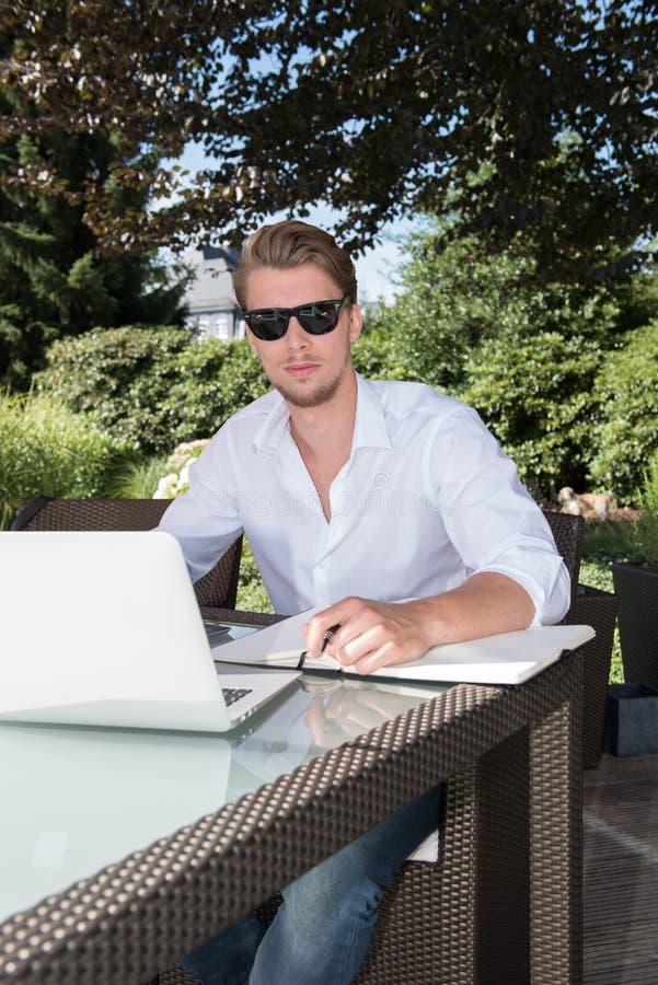 Uczeń pracuje z laptopem i książką w ogródzie obrazy stock