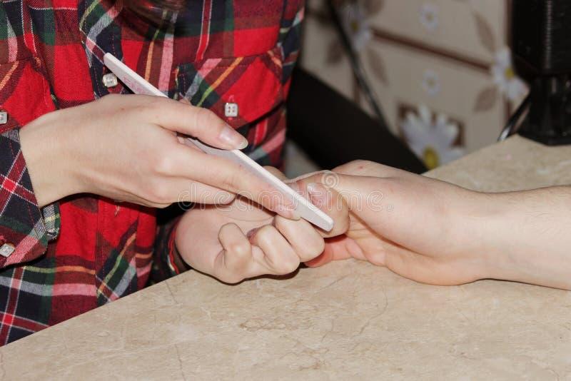 Uczeń przy kursami treningowymi manicure daje kształtowi gwoździe ręce mężczyzna klient z saw maniak zdjęcia stock