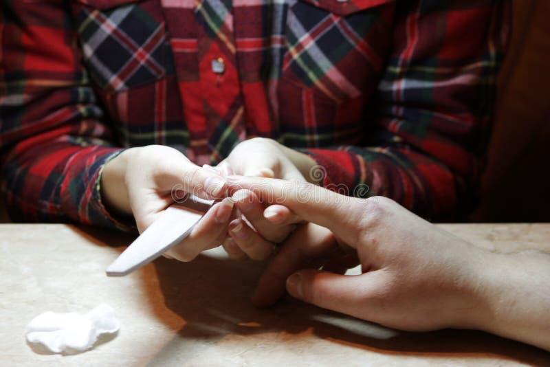 Uczeń przy kursami treningowymi manicure daje kształtowi gwoździe ręce mężczyzna klient z saw maniak zdjęcie stock