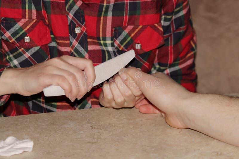 Uczeń przy kursami treningowymi manicure daje kształtowi gwoździe ręce mężczyzna klient z saw maniak obrazy stock