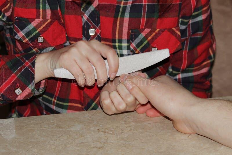 Uczeń przy kursami treningowymi manicure daje kształtowi gwoździe ręce mężczyzna klient z saw maniak obrazy royalty free