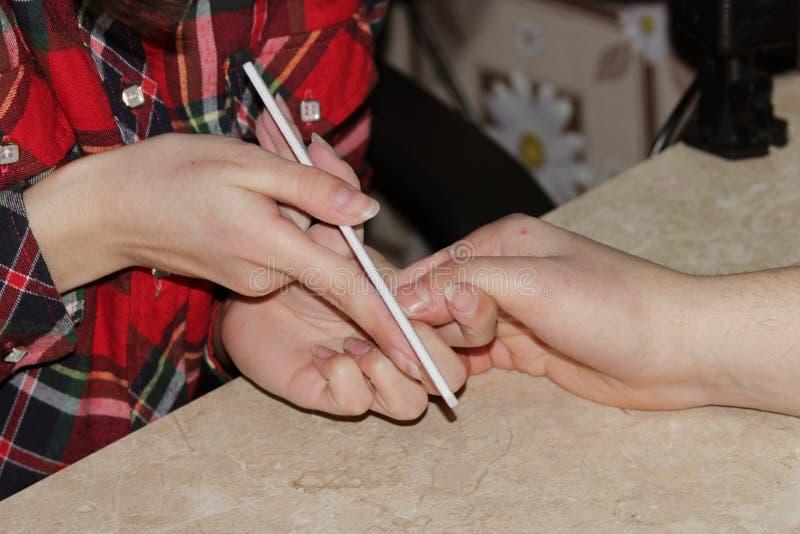 Uczeń przy kursami treningowymi manicure daje kształtowi gwoździe ręce mężczyzna klient z saw maniak fotografia royalty free