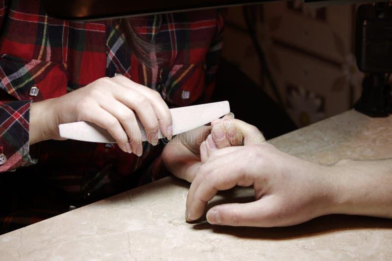 Uczeń przy kursami treningowymi manicure daje kształtowi gwoździe ręce mężczyzna klient z saw maniak obraz stock