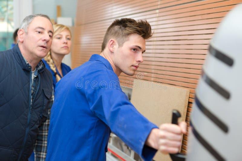 Uczeń stolarski demonstrujący działanie maszyny fotografia stock