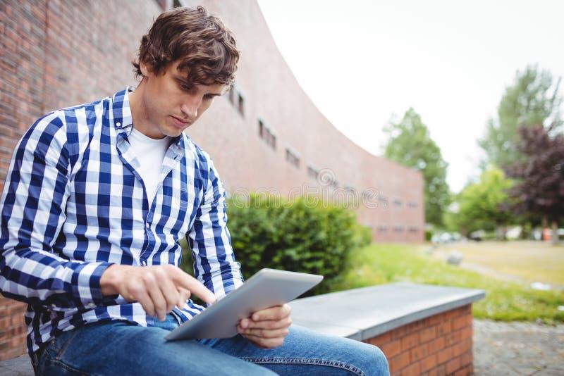 Uczeń używa cyfrową pastylkę w kampusie fotografia stock