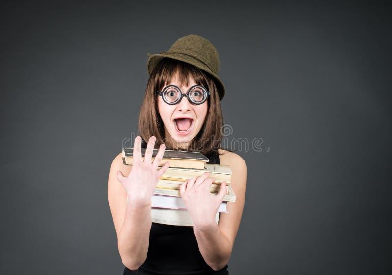 Uczeń w śmiesznych szkłach z książkami na popielatym Głupek dziewczyny studiowanie Edukacja fotografia stock