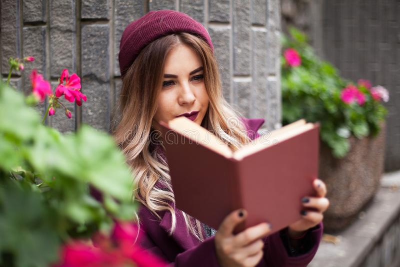 Uczeń w fioletowej kapeluszu czyta podręcznik na ulicy Zbliżenia, pionowo obraz royalty free