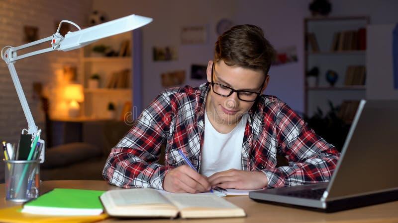 Ucze? w szk?ach robi pracie domowej, pisze eseju, otwiera ksi??k? i laptop na stole obrazy stock